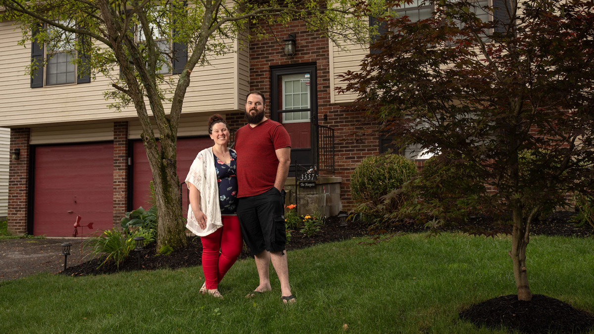Surrounded by trees and tidy landscaping, Courtney and Jonathan Hooper stand on the front lawn of their first home.