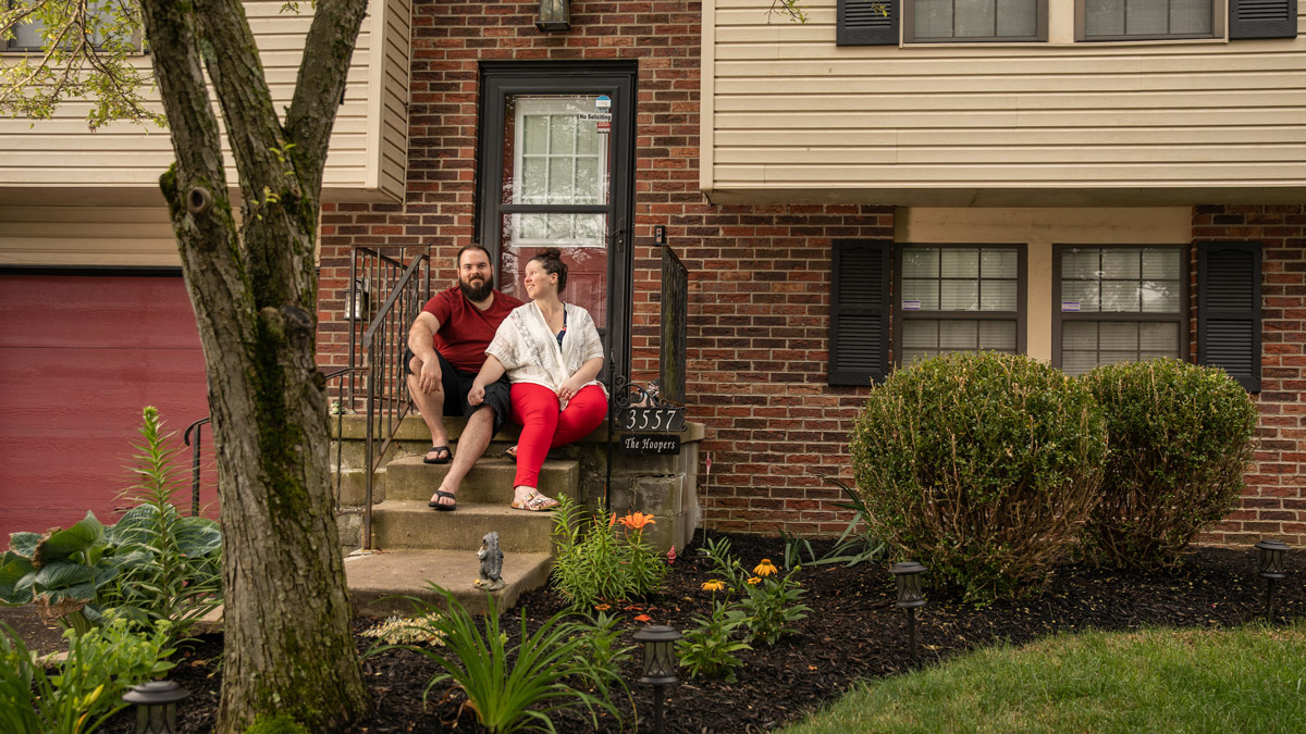 Man and woman sitting on steps in front of a house.